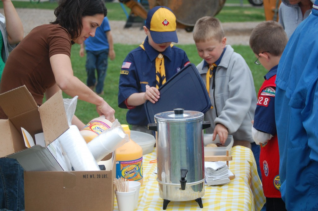 Village Trustee Chris Bucko (left) pours juice while Cub Scouts help themselves to a celebratory cookie or two.