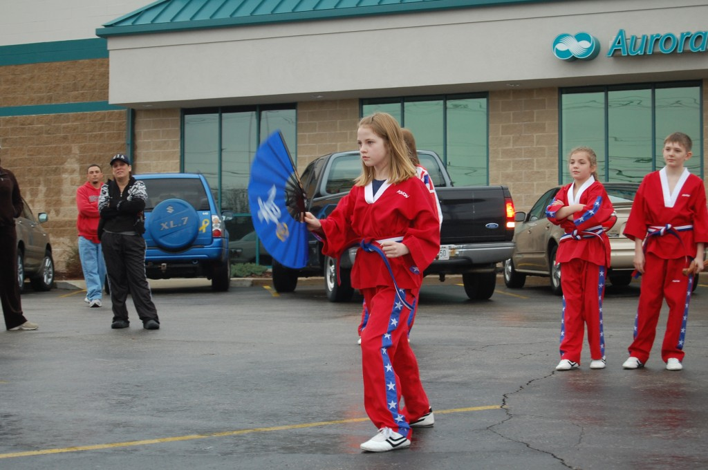 Maddie Murphy, a student at USA Martial Arts, demonstrates moves using a fan. The martial arts students gave their demonstration inbetween showers at the food drive.