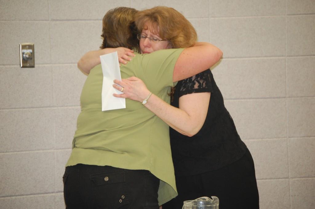 Salem Schol Board President Patricia Merrill (right) hugs board member Peggy Aull after Merrill announced her resignation Thursday night.
