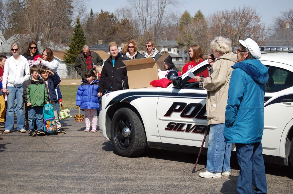 Phyllis Greenwood gives directions to the eager youngsters over the squad car PA while event organizer, Trustee Ann Augustin, looks on.