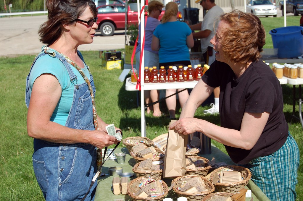 Barb Uhlenhakke of Bristol (left) purchases some goat milk soap from Laura Pulda, owner of Nature's Niche. Pulda performs every step in making her product, including caring for and milking the goats on her property south of Burlington.