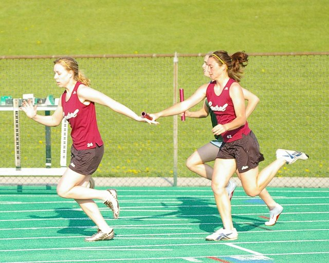 Central's Aubrey Mills takes the baton from Nica Ware on the way to winning the 800 relay.