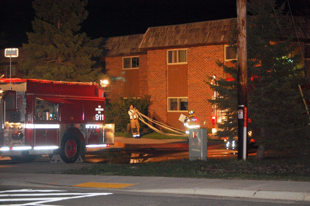 Firefighters retrieve hose at the scene of an excessive smoke call Friday evening.