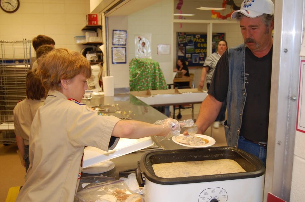 Scout Jonah Arbet serves some sausage gravy to Willia Lewis of Salem.