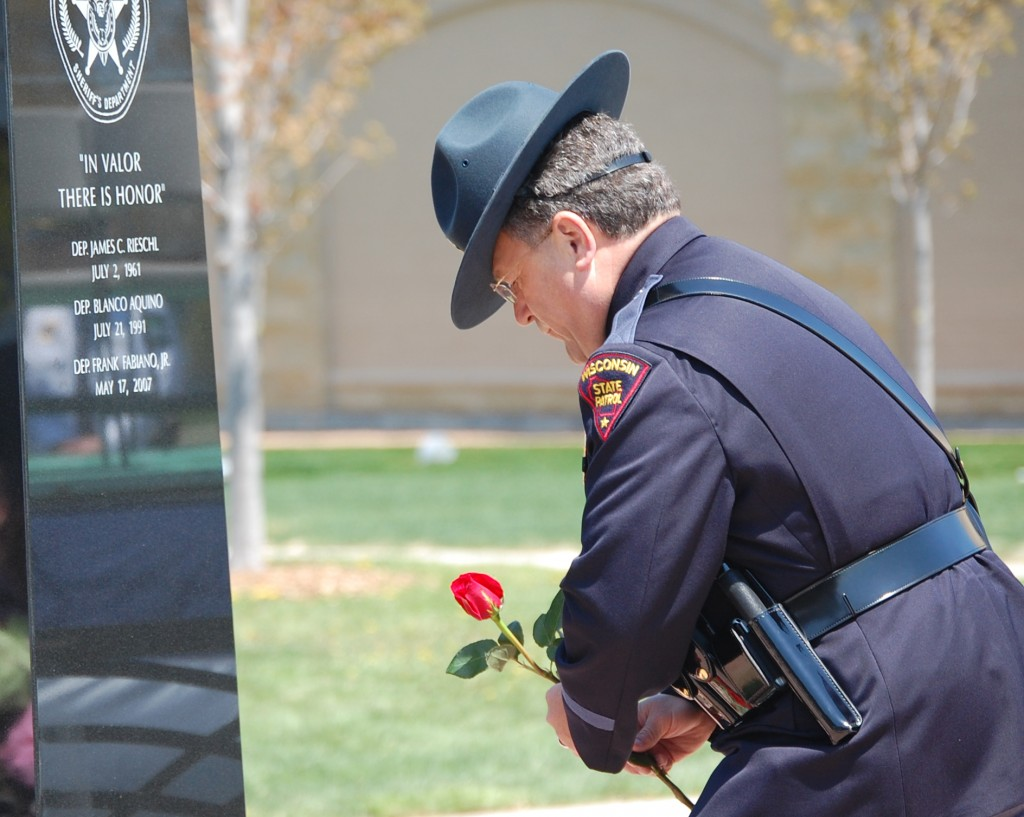 A state trooper lays a flower at the Kenosha Public Safety Mounument at the reading of the name of slain sheriff's Deputy Frank J. Fabiano Jr.