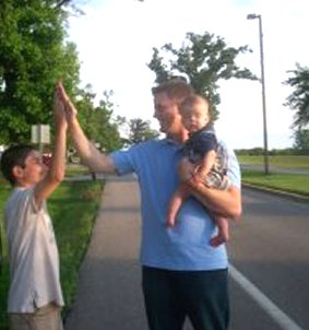 Father and sons take a stroll down 248th Ave in Paddock Lake. The Baker boys Jacob, 10, and Dad Rob high five, while the newest member of the family Ryan, 7 months, is ready for a nap.