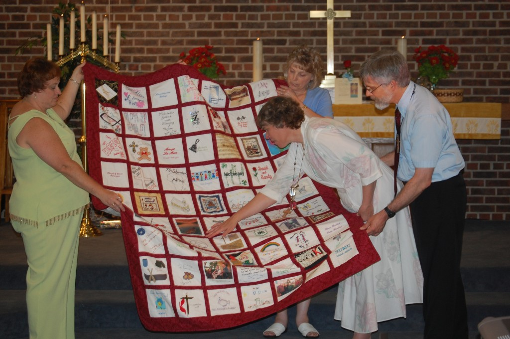 Ricki and Joe Mitchell, right, look over a quilt that church families at Salem United Methodist Church made for the couple. Joe Mitchell, who had been pastor of the church for 15 years before being reassigned, led his last service at the local church Sunday. Presenting the quilt are Kim Ouwkerk and Marcie Schultz.
