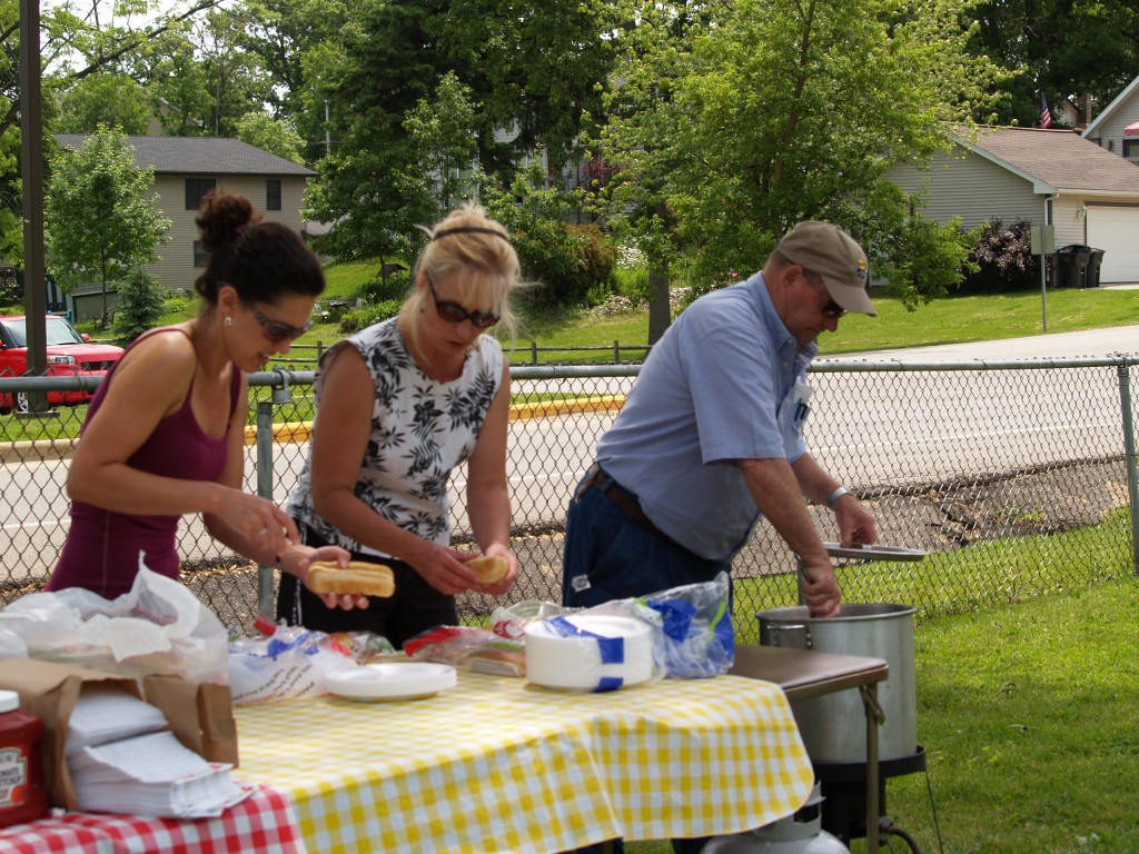 Chris Bucko, Karen Harris and Herman Weber serve hot dogs to hungry visitors