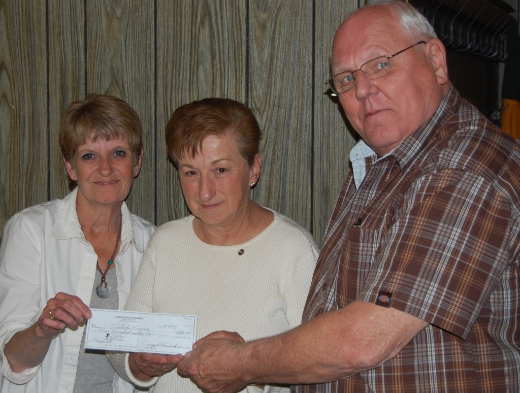 Joe Riesselmann hands a $500 check to Westosha Kiwanians Cheryl Paeth and Marge Smelzer to add to the club's 2009 fireworks dun. The club is trying a new way of funding the annual fireworks display in Paddock Lake that it previousily funded through a $100 a ticket raffle.
