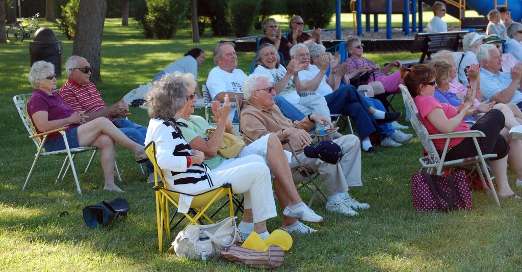 Audience members in the coveted shady section show their appreciation for the Crawford band.