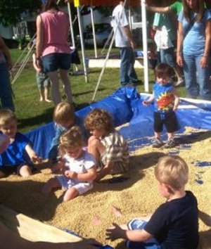 Area children enjoyed playing and even burying their legs in the soybean box.