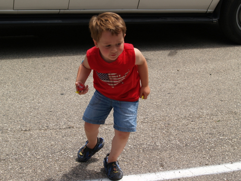 Two-year-old Aiden Burns races to fill his bag with parade candy