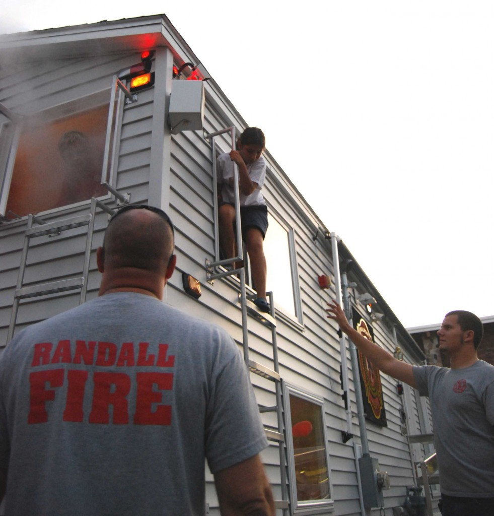 """Randall Firefighters John Love and David Wyakowenko assist a girl exiting the Walworth County Firefighters Association """"Survive Alive Fire Safety Smoke House and Sprinkler Trainer."""" This was one of the educational exhibits at the National Night Out event Tuesday in Twin Lakes. /Photo by Andrew Strother"""