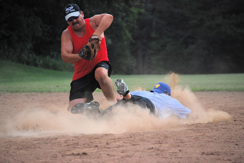 Firefighter Mark Jaslowski scoops up a throw to second base as the runner slides under the tag. /Andrew Strother photo