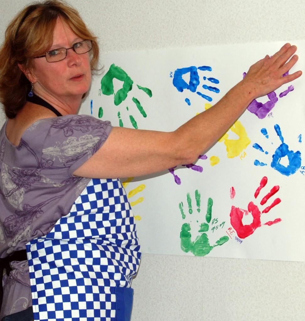 Center volunteer Karen Rasmussen puts up on the wall some of the handprints collected Saturday.