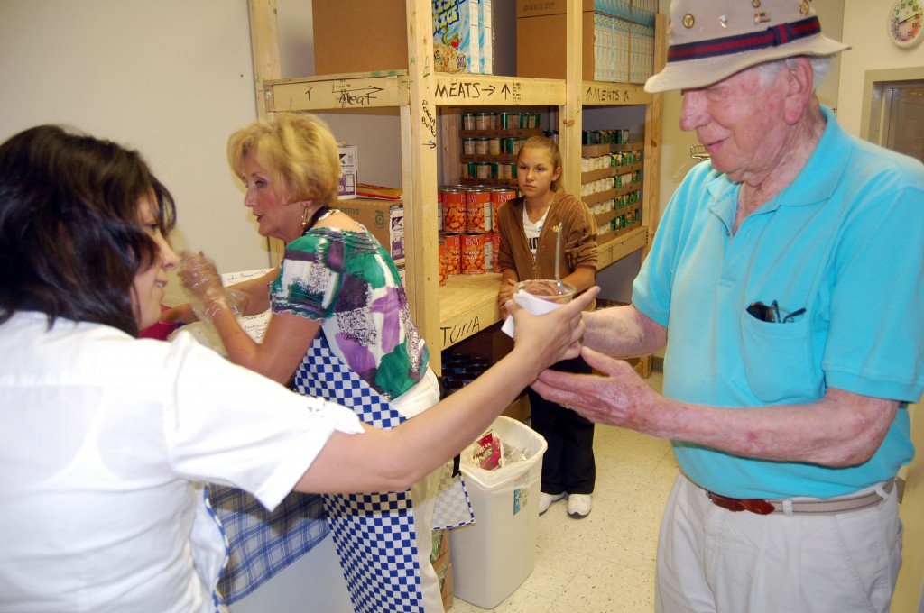 Cal Hewitt (right) accepts some ice cream from The Sharing Center board member Maria Dillman (far left). Those who attended the center's open house were treated to some desert.