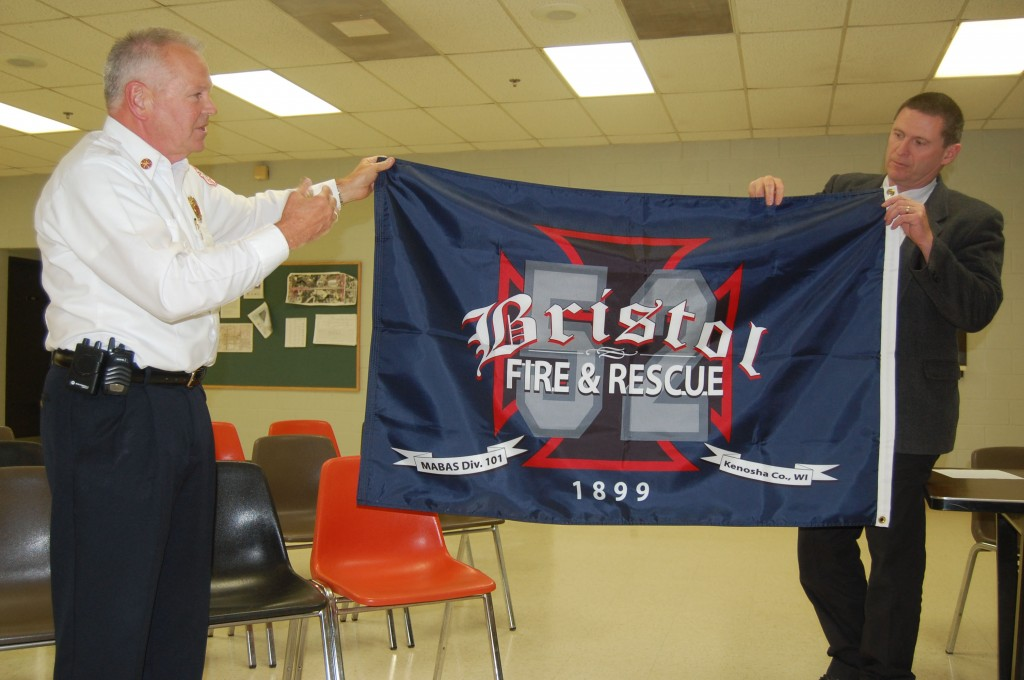 Bristol Fire Chief Peter Parker (left) explains some of the components of the new fire department flag design to the Town Board Monday night. Town administrator Randy Kerkman holds the other end of the flag.