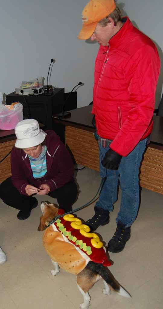 Edgar won first prize for his hot dog costume. Here he gets a treat from Anita Perrin while Bruce Giles looks on.