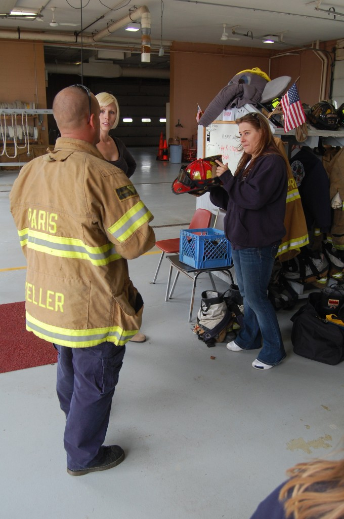 Kim Kromm (right) takes a closer look at a firefighter's helmet while chatting with Lt. Jacob Keller.