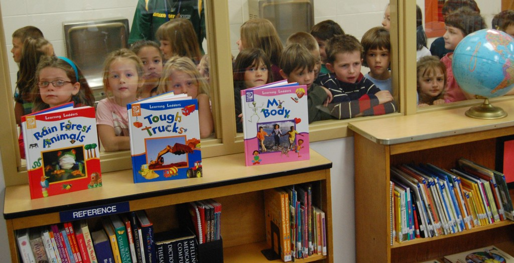 Eager students take a peek at their new library from the hallway through the windows in the library's new walls.