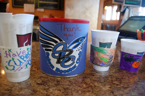 A display of some of the coffee sleeves available at Brewed Beginnings in Paddock Lake that were decorated by Salem School students. Jim and Debi Rigney. the shop's owners, are giving donations customers make to the Salem Booster Club.