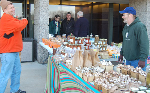 Mike Ehlers of River Valley Ranch, New Munster, (right) talks mushrooms with a visitor to the farmer's market.