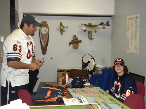 """Chicago Bear offensive lineman Roberto Garza signs some Bears items while chatting with student David Hunt at Bristol School Tuesday. Hunt was a winner in the NFL's """"Bring a Player to School"""" contest. /Photo by Lisa Weiner"""