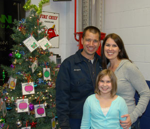 The Garwoods and their Anonymous Angels Christmas tree. People can pick the information for a family to adopt through The Sharing Center's Anonymous Angels program at the Garwood's business, Wilmot Auto Service, Highways C and W, Wilmot, from 7 a.m. to 6 p.m. Monday through Friday.