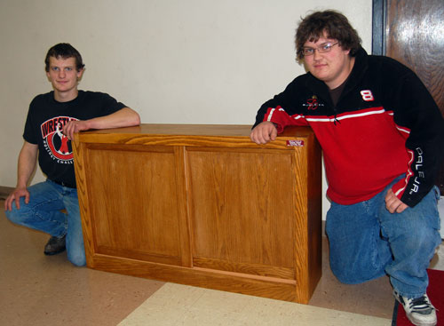 Nick Able and Gary Kreuger pose with the cabinet they made for Paris School.