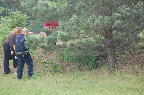 Constable Bob Haas and a Kenosha County Sheriff's Department detective discuss the scene while other detectives gather evidence behind a line of trees. This westofthei.com file photo was taken on June 15, 2010 after a person Haas pulled over, showed a weapon fled and led police on a lengthy manhunt.