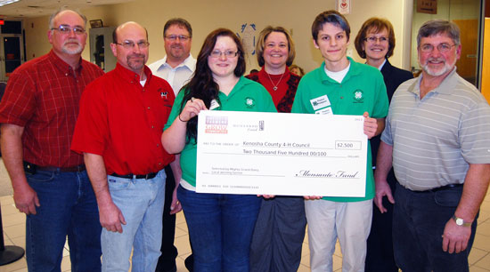 Brenda Hafeman, president, Kenosha County 4-H Councll, and two otehr 4-H represetnatives accept a $2,500 donation from Mighty Grand Dairy's Myron Daniels, Gene Weis and Dave Daniels as well as Growmark/CONSERV FS representatives Joe Terando and :Laura Rowe.