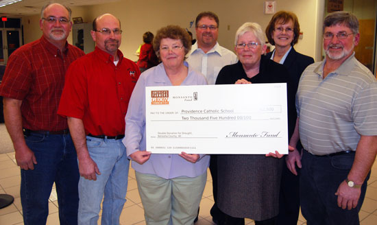 Providence Catholic School teacher Sue Kaminski and Principal Sue Meyer (front row center) accept a $2,500 donation from Mighty Grand Dairy partners (also front row) Myron Daniels, Gene Weis and Dave Daniels and Growmark/CONSERV FS representatives Joe Terando and Laura Rowe.