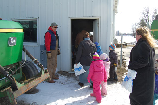 John Holloway welcomes students, chaperons and teachers to his farm's shop building.