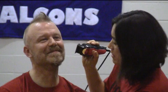 Salem School gym teacher John Stewart gets his head shaved by sixth grade teacher Mindy Stewart, who also is his wife.