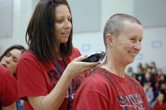 Kindergarten teacher Kerrie Ellis puts the final touches on Chris Seymour's hair cut.