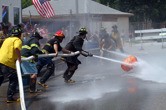 A Trevor team battles a Silver Lake team in the  firefighters water fights on Saturday. /Earlene Frederick photo