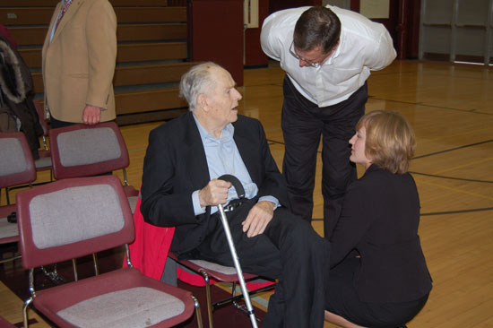 Leah Holloway (right) chats with her grandfather, veteran and Central High School founder Lloyd Holloway (seated) and her father and current School Board member John Holloway (standing) after the Assembly.