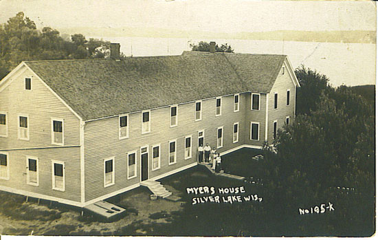 This image is the Myers House, a one time Boyle ICe Company boarding house of Silver Lake. This is the southerly exposure with the Cogswell Road and Silver Lake to the right side. This was located approximately where the storage units are next to Harm Garwood's BP Gas and Silver Lake Service Station is today. In this image, an addition has been made to the left of the chimney on to what was originally the boarding house. Over the years, the building hosted several different businesses and names including Bachara;s Hotel (1950s). It has since been torn down - June, 1990. From this boarding house location, the Boyle Ice House was directly across Cogswell. Best guess on the date of this image is 1907. /Submitted photo used with permission