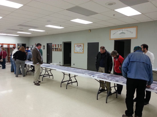 Residents examine a long aerial photo of the Hwy. 45 project with an overlay of the project's improvements.