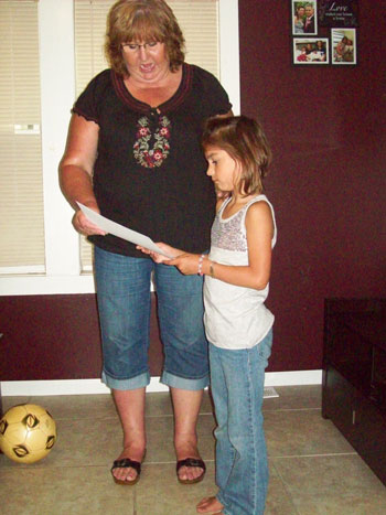 Patti Robinson presents a certificate to her granddaughter Olivia Lopez. /Contributed photo