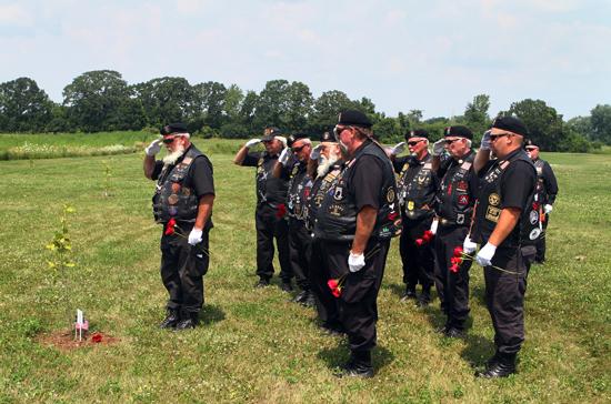 American Legion Riders lay roses by each tree.