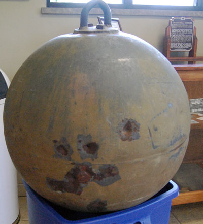 The donated brass ball. The origin of the dents is not known for sure. Some feel they might be from bullets fired at teh ball when it was performing its first duty as a mine buoy. Other think they were made when local folks took a few shots at the landmark as a lark.