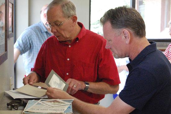 Jim Huntoon and village President Terry Burns look over some of Huntoon's historical mementos.